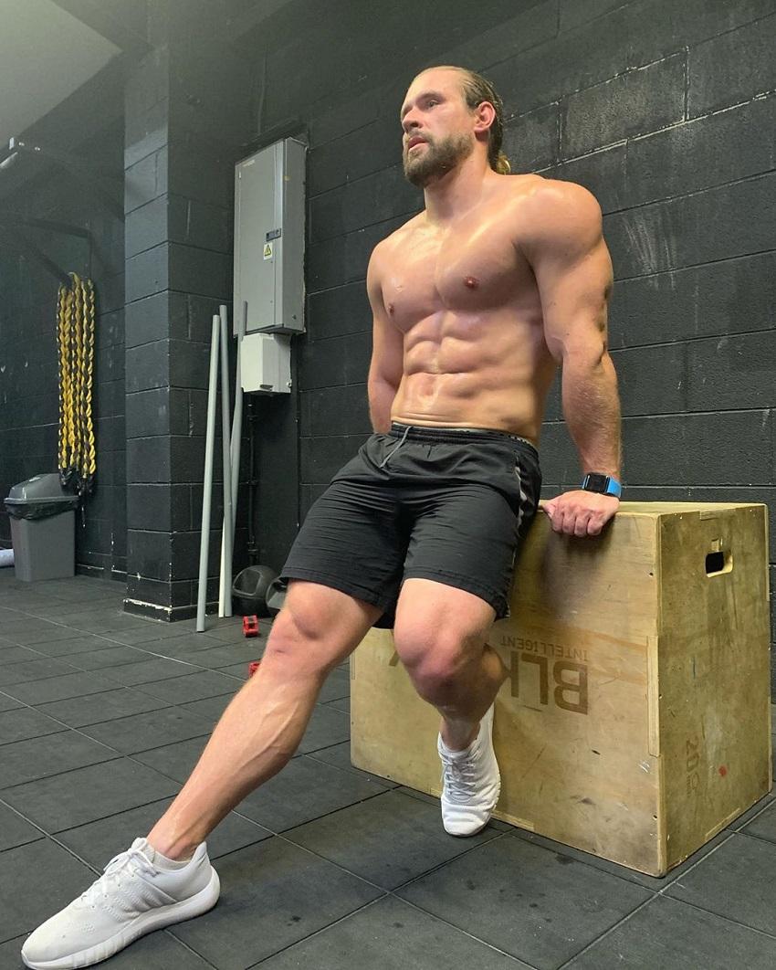 Ben Mudge sitting shirtless in the gym