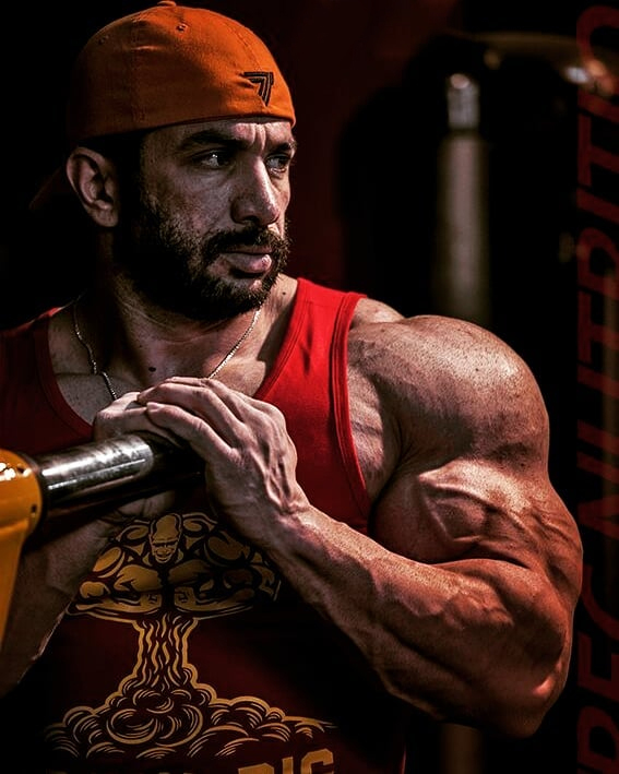 Mojtaba Notarki posing next to a squat bar, looking huge