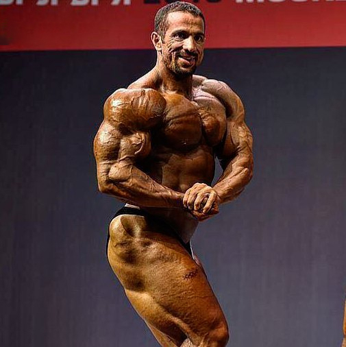 Mojtaba Notarki flexing side chest on the bodybuilding stage
