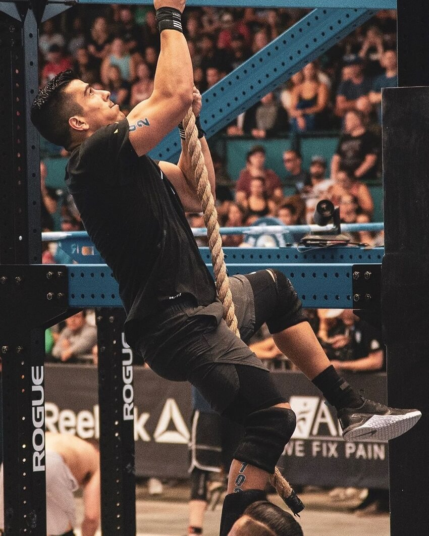 Garret Fisher climbing a rope during a CrossFit competition