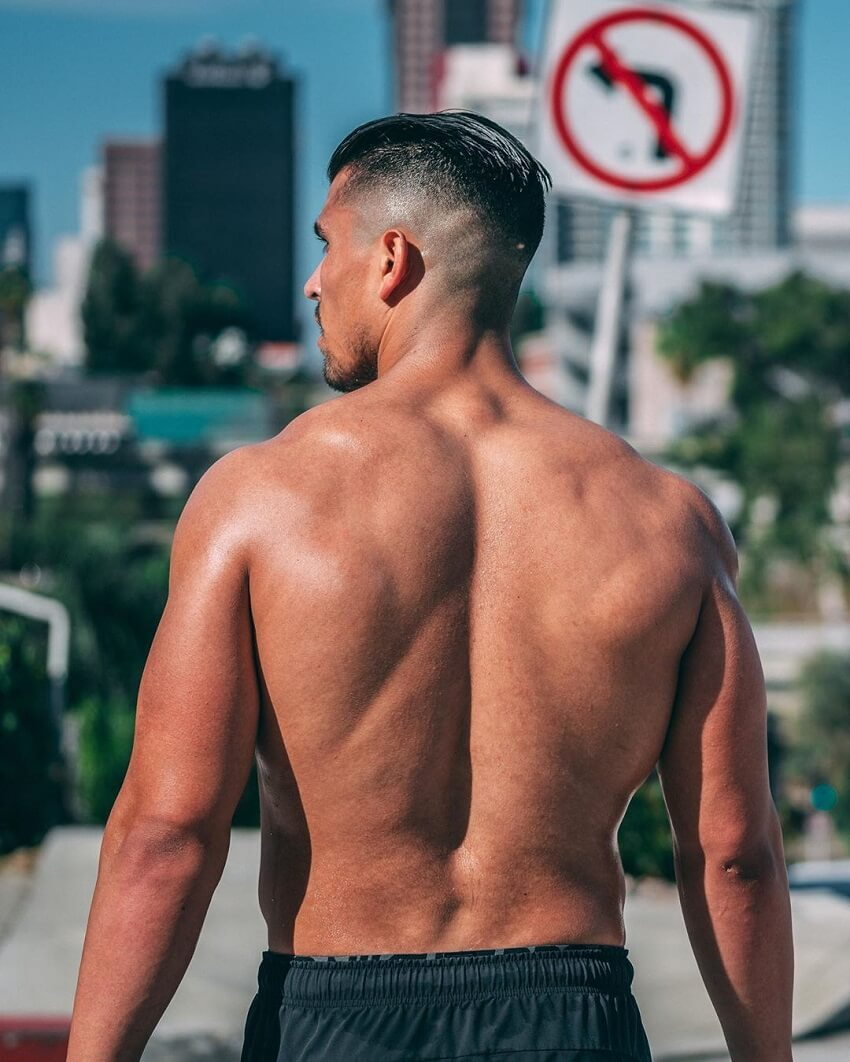 Garret Fisher strolling shirtless down the beach, with his back looking wide and muscular