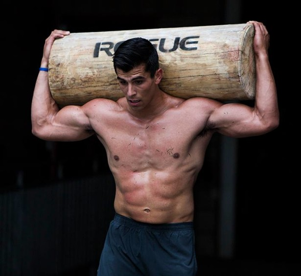 Garret Fisher shirtless, carrying heavy log over his head
