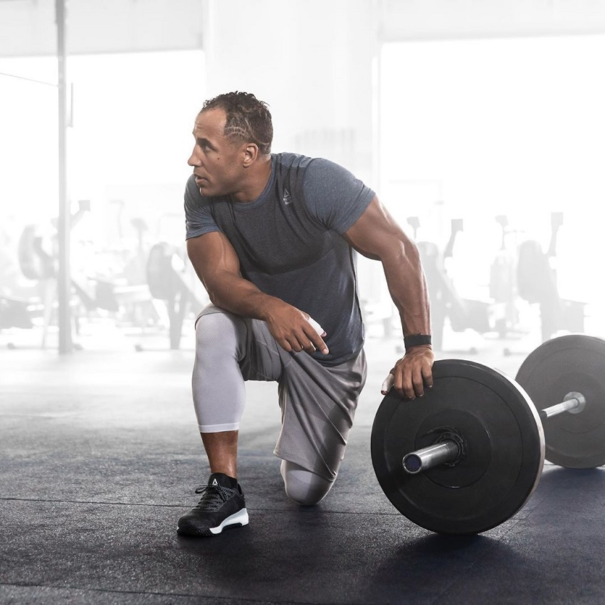 Neal Maddox leaning on a barbell in the gym