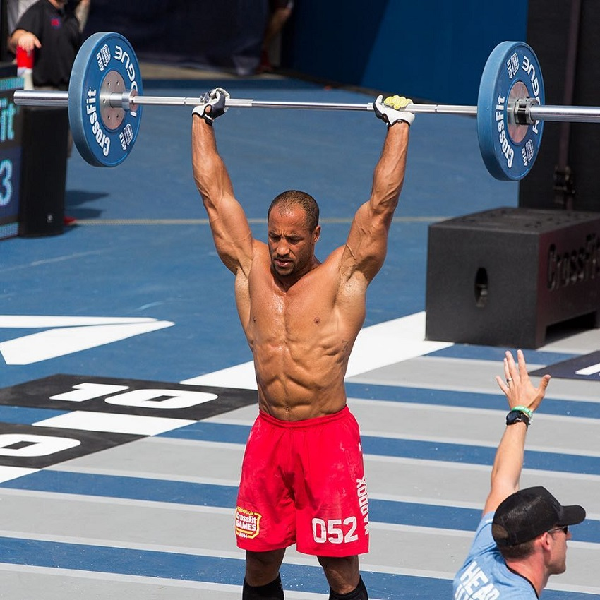 Neal Maddox shirtless, doing overhead barbell press during CrossFit Games