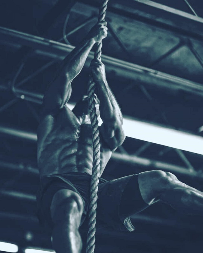 Neal Maddox climbing ropes during CrossFit training