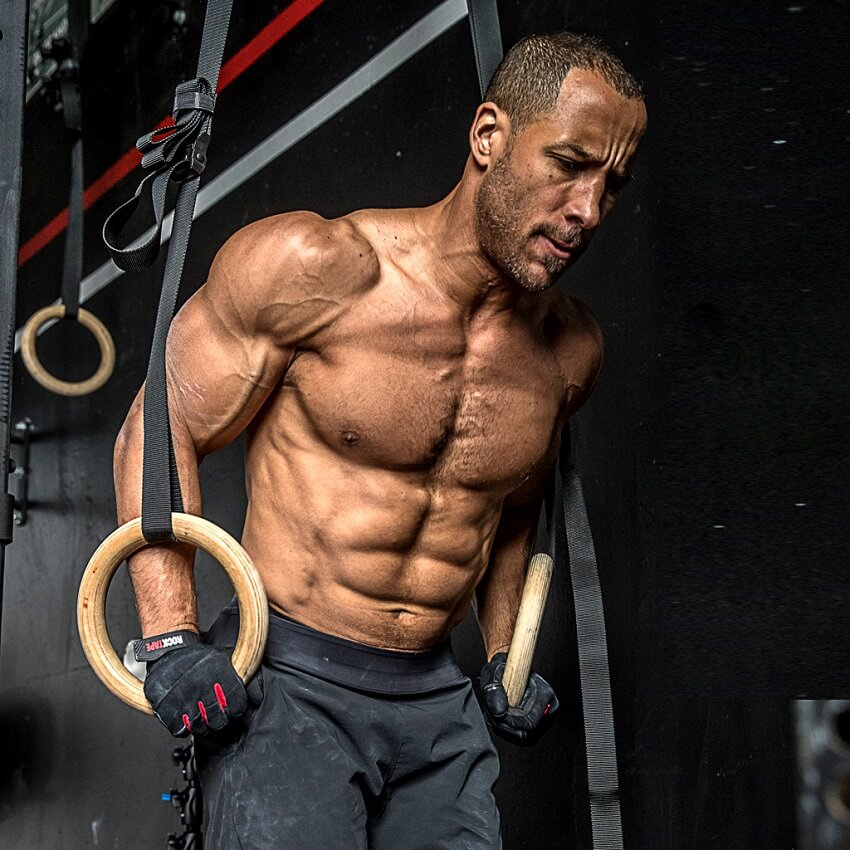 Neal Maddox training shirtless on rings, looking ripped and muscular