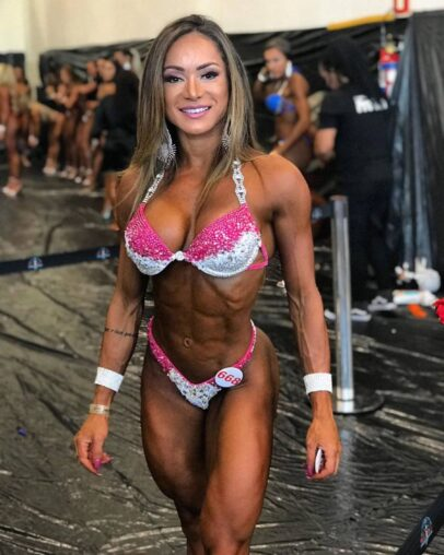 Susana Rodriguez posing backstage in her bikini, looking ripped and aesthetic