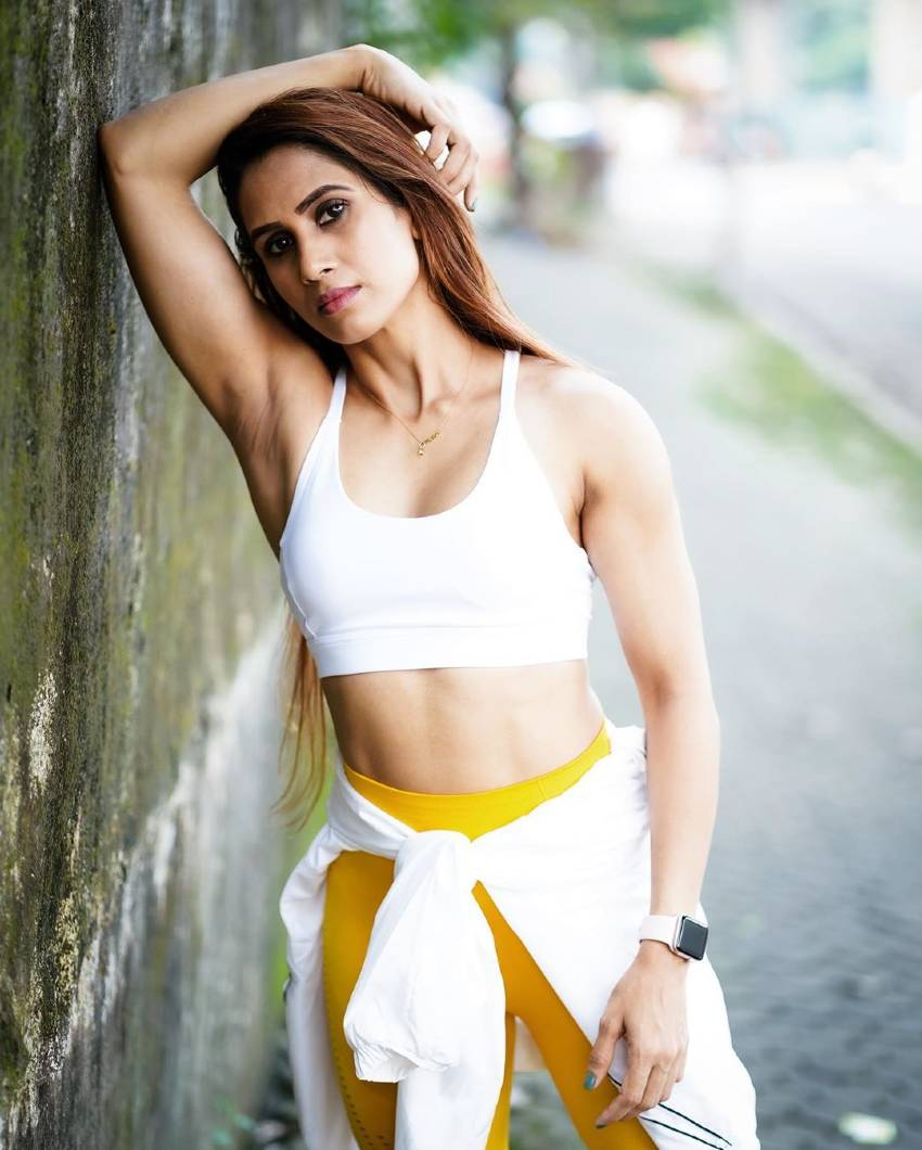 Vaishali Bhoir leaning against a wall wearing a fitness outfit, looking lean and toned